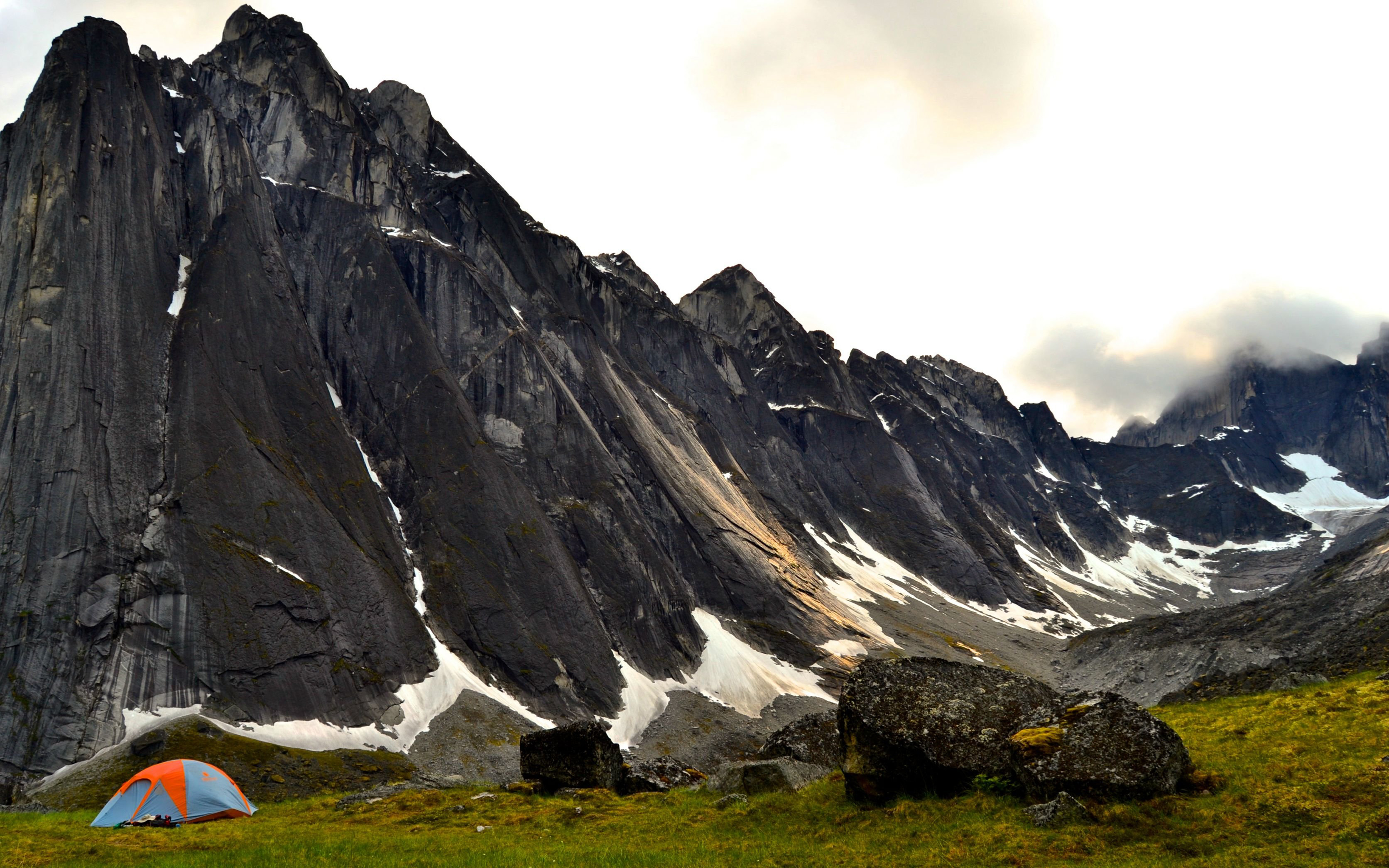 Nahanni-National-Park-Reserve-of-Canada-Mountains-rock-sharp-mountain-peaks-snow-closed-sky-with-clouds